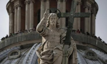 The statue of the Christ is seen in front of the dome of Saint Peter's Basilica at the Vatican