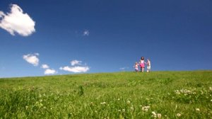 stock-footage-woman-with-children-holding-hands-descend-hill-with-green-grass